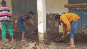 Women clear the school of over half a metre of oozing mud